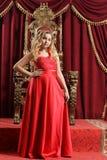 Blonde Jugendliche im hellen roten Kleid, das vor vin steht Stockbild