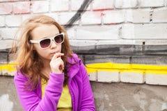 Blonde Jugendliche mit Lutscher, vertikales städtisches Porträt Lizenzfreie Stockfotos