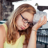 Blonde Jugendliche setzt Eis zum Kopf Lizenzfreie Stockfotos