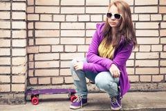 Blonde Jugendliche in Sonnenbrille mit Skateboard sitzt Stockbild