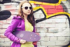 Blonde Jugendlichegriffe Skateboard, Porträt Lizenzfreies Stockbild