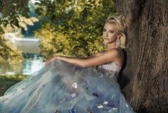 Blonde junge Dame, die auf dem Baum sich lehnt Stockfotos