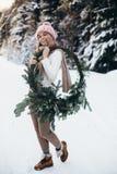 Blonde junge Dame mit Weihnachtskranz im Winterwald Stockfoto