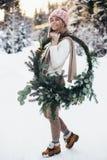 Blonde junge Dame mit Weihnachtskranz im Winterwald Stockbilder