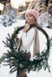 Blonde junge Dame mit Weihnachtskranz im Winterwald Stockbild