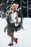 Blonde junge Dame mit Weihnachtskranz im Winterwald Lizenzfreies Stockbild