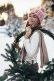 Blonde junge Dame mit Weihnachtskranz im Winterwald Lizenzfreies Stockfoto