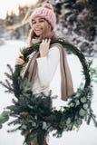 Blonde junge Dame mit Weihnachtskranz im Winterwald Stockfotografie