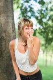 Blonde junge draußen lachende und versteckende Frau Lizenzfreies Stockbild