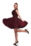 Blonde junge elegante Frau, die ein Bein anhebt Stockbild