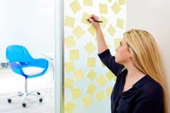 Blonde junge Exekutive mit Aufklebern im Büro Lizenzfreie Stockfotografie