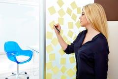 Blonde junge Exekutive mit Aufklebern im Büro Lizenzfreies Stockfoto