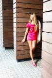 Blonde junge Frau in der rosa Kleideraufstellung Lizenzfreie Stockfotografie
