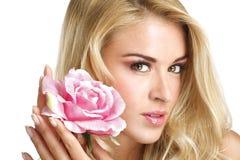 Blonde junge Frau der Schönheit, die eine frische Blume auf Weiß zeigt Lizenzfreie Stockbilder