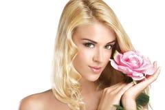 Blonde junge Frau der Schönheit, die eine frische Blume auf Weiß zeigt Stockbild