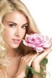 Blonde junge Frau der Schönheit, die eine frische Blume auf Weiß zeigt Lizenzfreies Stockfoto