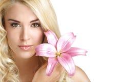 Blonde junge Frau der Schönheit, die eine frische Blume auf Weiß zeigt Lizenzfreies Stockbild