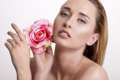 Blonde junge Frau der Schönheit, die eine frische Blume auf Weiß zeigt Lizenzfreie Stockfotografie