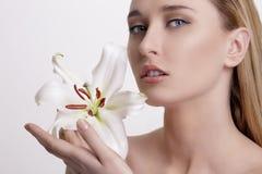 Blonde junge Frau der Schönheit, die eine frische Blume zeigt Lizenzfreies Stockbild