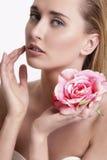 Blonde junge Frau der Schönheit, die eine frische Blume zeigt Stockfotografie