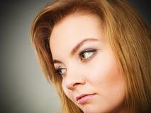 Blonde junge Frau des Porträts, die ernsten Gesichtsausdruck hat Stockbild
