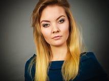 Blonde junge Frau des Porträts, die ernsten Gesichtsausdruck hat Stockfoto
