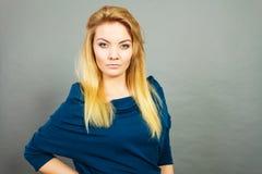 Blonde junge Frau des Porträts, die ernsten Gesichtsausdruck hat Stockfotografie