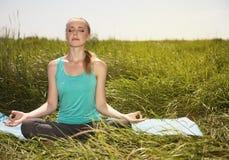 Blonde junge Frau des ruhigen gesunden Sitzes, die auf der Natur meditiert Stockbilder