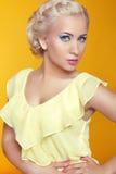 Blonde junge Frau, die über gelbem Hintergrund aufwirft Lizenzfreie Stockbilder
