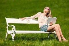 Blonde junge Frau, die auf Bank mit Buch sitzt Lizenzfreie Stockbilder