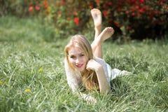 Blonde junge Frau, die auf dem Gras mit den angehobenen Beinen liegt Reizendes im Frühjahr lächeln des Mädchens und genießendes b Stockfoto