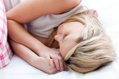 Blonde junge Frau, die auf einem Bett schläft Lizenzfreie Stockfotografie