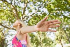 Blonde junge Frau, die auf einem Rasen steht Stockfotografie