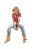 Blonde junge Frau, die auf einer Fahne sitzt Stockfotografie