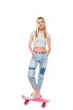 Blonde junge Frau, die auf Skateboard steht und an der Kamera lokalisiert auf Weiß lächelt Stockfoto