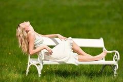 Blonde junge Frau, die auf weißer Bank sitzt Lizenzfreie Stockfotos