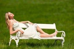 Blonde junge Frau, die auf weißer Bank sitzt Lizenzfreies Stockbild