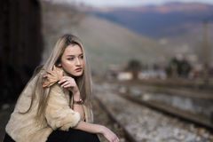 Blonde junge Frau, die an der Randeisenbahnplattform sitzt Stockfoto