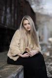 Blonde junge Frau, die an der Randeisenbahnplattform sitzt Lizenzfreie Stockbilder