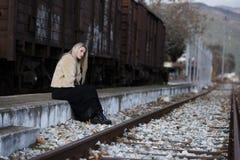 Blonde junge Frau, die an der Randeisenbahnplattform sitzt Stockfotografie