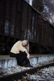Blonde junge Frau, die an der Randeisenbahnplattform sitzt Stockfotos