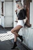 Blonde junge Frau, die draußen aufwirft Stockbild