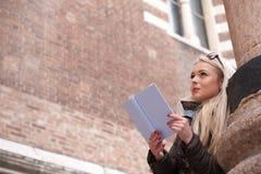 Blonde junge Frau, die draußen ein Buch liest Stockbild