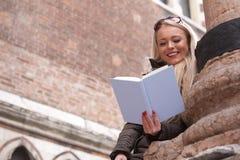Blonde junge Frau, die draußen ein Buch liest Stockfoto