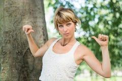 Blonde junge Frau, die draußen Finger auf zeigt Stockfotografie