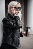 Blonde junge Frau, die draußen mit Kaffee aufwirft Lizenzfreie Stockfotografie