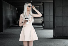 Blonde junge Frau, die draußen mit Kaffee aufwirft Stockbild