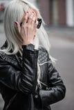 Blonde junge Frau, die draußen mit Uhr aufwirft Stockbilder