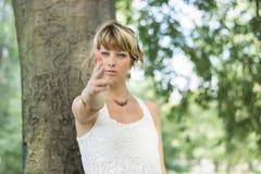 Blonde junge Frau, die draußen vortäuscht zu schießen Stockfotografie