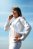 Blonde junge Frau, die durch Handy benennt Stockbilder